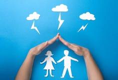 Lebensversicherung und Familiengesundheitskonzept Hände schützen Papierzahlen Origami vor Blitz von den Wolken auf blauem Hinterg Stockbilder