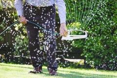 Lebenwasserspr?her des Mannes unter Verwendung der D?sen, zum des Gartengrases w?hrend der hei?en trockenen Sommersaison zu hydra stockbilder