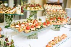 lebesmittelanschaffung Externe Nahrung Buffettisch mit verschiedenen Canapes, Sandwichen, Hamburgern und Imbissen lizenzfreie stockfotos