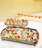 Lebesmittelanschaffungnahrung in den silbernen Tellern mit Wein Stockfoto