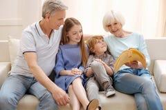 Lebhafte erfinderische Paare, die ihre Enkelkinder unterhalten lizenzfreie stockbilder