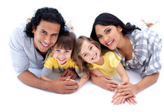 Lebhafte Familie, die auf dem Fußboden liegt Stockbilder