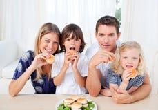 Lebhafte Familie, die Burger im Wohnzimmer isst Stockbilder