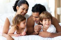 Lebhafte Familie, die Spaß hat, auf Bett zu liegen Lizenzfreie Stockfotos