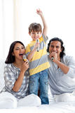 Lebhafte junge Familie, die mit Mikrophonen singt Stockbilder