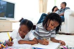 Lebhafte Kinder, die das Lügen auf dem Fußboden zeichnen Lizenzfreie Stockbilder