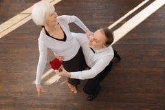 Lebhafter gealterter Mann, der mit seiner Frau im Ballsaal tangoing ist Stockfotos