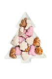 Lebkuchen biscuits in a dish. Lebkuchen, German spiced biscuits in a Christmas tree shaped dish isolated against white Stock Image