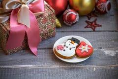 Lebkuchen-Mann über Holz Lebkuchen-, Weihnachtsdekorationen und Geschenkbox Stockbild