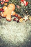 Lebkuchen-Mann mit Gewürzen, Tannenbrunchs und festlicher Weihnachtsdekoration auf rustikalem Weinlesehintergrund Lizenzfreies Stockfoto