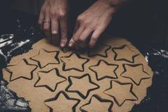 Lebkuchen-Mann-Plätzchen-Teig-Ausschnitt durch junges Mädchen zur Weihnachtszeit Stockfotografie