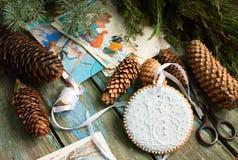 Lebkuchen mit einem Bild eines Schneemannes, der Tannenzapfen, der Niederlassungen und der Postkarten auf einem hölzernen Hinterg Lizenzfreies Stockfoto