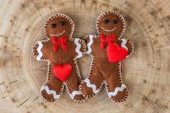Lebkuchen mit zwei Geweben mit Herzen auf hölzernem Hintergrund, lustige Liebesgeschichte am Valentinsgrußtag Stockbilder