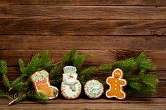 Lebkuchen: Socke, Schneemann, Ball und Hahn, Fichtenzweig auf einem Hintergrund einer hölzernen Wand Stockfotos