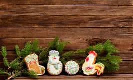Lebkuchen: Socke, Schneemann, Ball und Hahn, Fichtenzweig auf einem Hintergrund einer hölzernen Wand mit Raum für Text Lizenzfreies Stockbild