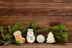 Lebkuchen: Socke, Schneemann, Ball und Tannenbaum, Fichtenzweig auf einem Hintergrund einer hölzernen Wand Stockfotografie
