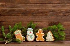 Lebkuchen: Socke, Schneemann, Mann, Tannenbaum, Fichtenzweig auf einem Hintergrund einer hölzernen Wand Lizenzfreie Stockfotos