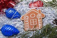 Lebkuchenhaus mit Weihnachtsspielwaren und -lametta Stockfotografie