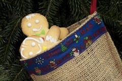 Lebkuchenjungen-Umarmungsmädchen in der Weihnachtssocke Lizenzfreies Stockbild
