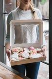 Lebkuchenkasten mit weiblichem Kurier Lebensmittellieferung stockbild