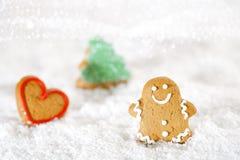 Lebkuchenmann und -baum auf einem festlichen Weihnachtsschneehintergrund stockfotos