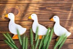 Lebkuchenplätzchen formten Ente mit dem Ohr des Weizens auf einem hölzernen Hintergrund Stockbilder