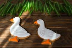Lebkuchenplätzchen formten Ente mit dem Ohr des Weizens auf einem hölzernen Hintergrund Stockfotografie
