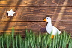 Lebkuchenplätzchen formten Ente mit dem Ohr des Weizens auf einem hölzernen Hintergrund Flache Schärfentiefe Lizenzfreie Stockfotografie