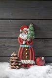 Lebkuchenweihnachtsmann-Weihnachtsbirnenschokoladen-Weihnachtsbaum auf Haufen des Schnees gegen hölzernen Hintergrund Lizenzfreies Stockbild