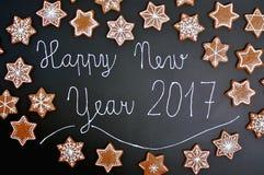 Lebkuchenweihnachtsplätzchen spielt und Schneeflocken mit Textguten rutsch ins neue jahr 2017 auf schwarzem Hintergrund die Haupt Lizenzfreie Stockfotografie