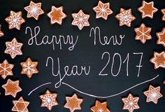Lebkuchenweihnachtsplätzchen spielt und Schneeflocken mit weißer Zuckerglasur mit frohen Weihnachten des Textes auf schwarzem Hin Stockfotografie