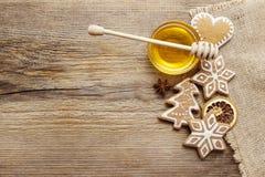 Lebkuchenweihnachtsplätzchen und Schüssel Honig auf Holztisch Lizenzfreie Stockfotos