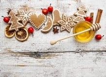 Lebkuchenweihnachtsplätzchen und Schüssel Honig auf Holztisch Stockfotos