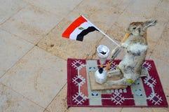 A lebre cinzenta está no tapete que guarda a bandeira egípcia em suas patas e que fuma um cachimbo de água, um espantalho foto de stock