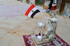 A lebre cinzenta está no tapete que guarda a bandeira egípcia em suas patas e que fuma um cachimbo de água, um espantalho fotos de stock