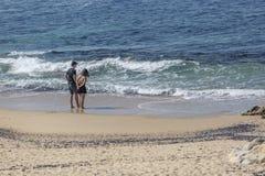 Leca da Palmeira/Porto/Portugal - 10 04 2018: Sikt på ett par, bara på stranden som talar och tycker om på stranden av Leca da royaltyfri fotografi