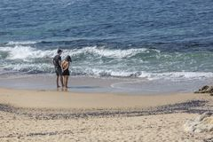 Leca da Palmeira/Porto/Portugal - 10 04 2018: View at a couple, alone on the beach, talking and enjoying on the beach of Leca da royalty free stock photography