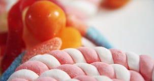 Lecca-lecca e caramelle su fondo bianco 4k video d archivio