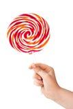 Lecca-lecca di colore in mano del bambino su bianco fotografie stock