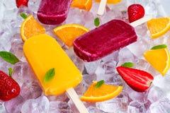 Lecca lecca di rinfresco del ghiacciolo della frutta sul fondo con le bacche, menta piperita del ghiaccio Immagini Stock