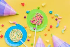 Lecca-lecca e cappelli del partito per il buon compleanno sul copyspace giallo di vista superiore del fondo Immagine Stock