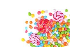 Lecca-lecca multicolori e caramelle rotonde su un fondo bianco Immagine Stock