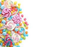 Lecca-lecca multicolori e caramelle rotonde su un fondo bianco Isolato Fotografia Stock Libera da Diritti