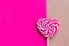 Lecca-lecca rosa di forma del focolare di giorno di S. Valentino sui precedenti blu immagini stock libere da diritti