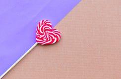 Lecca-lecca rossa di forma del focolare di giorno di S. Valentino sui precedenti viola immagini stock