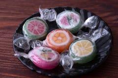 Lecca-lecca variopinte e caramella rotonda colorata differente della frutta nel wr Immagini Stock