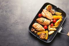 Leccarda con i seni di pollo fritto e contorno su fondo grigio, vista superiore fotografia stock