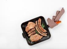 Leccarda del ghisa con bistecca e le salsiccie grigliate Fotografia Stock