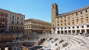 LECCE, ITALIA - 2 AGOSTO 2017: Anfiteatro romano con i palazzi del Sedile e del delle Assicurazioni di INA Istituto Nazionale Immagini Stock Libere da Diritti