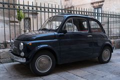 Black Fiat vintage cinquecento 500 car parked in front of railings outside church in Puglia, Southern Italy.